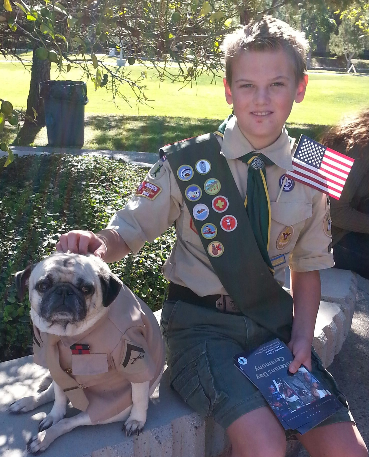 a boy scout beside a dog